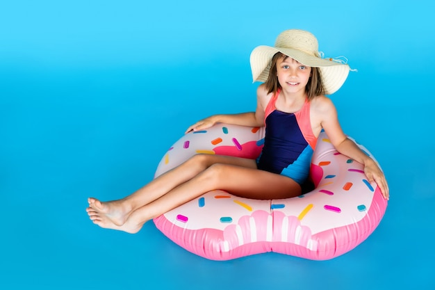 Cute girl in blue swimsuit and straw hat with huge nflated rubber ring