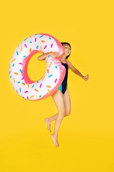 Cute girl in blue swimsuit with huge nflated rubber ring jumping on yellow