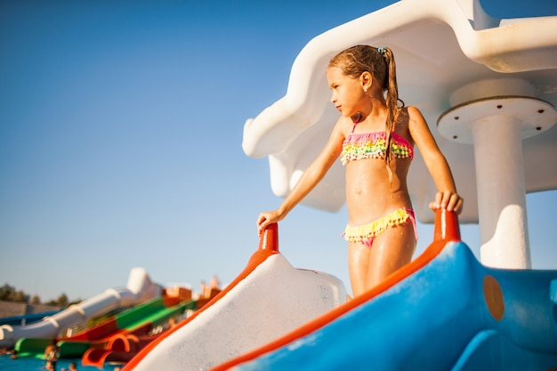A cute girl in a bright bathing suit stands on a slide, and prepares to go down from it to a pool with clear transparent water