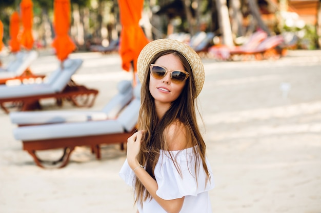 Cute girl in brown sunglasses and straw hat smiles charmingly.