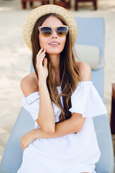 Cute girl in brown sunglasses and straw hat smiles widely and holds her hand near chin.