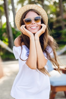 Cute girl in brown sunglasses and straw hat smiles widely and holds her hands near chin.