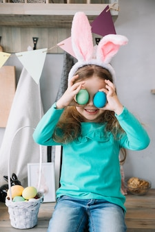 Cute girl in bunny ears holding colored eggs at eyes