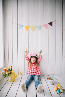 Cute girl in bunny ears holding easter eggs in hands