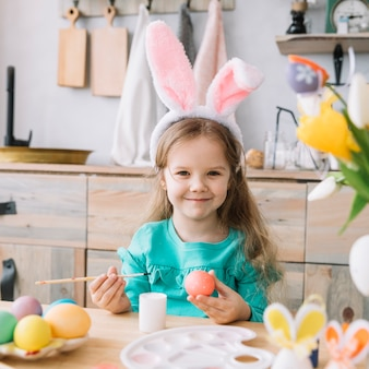 Cute girl in bunny ears painting eggs for easter