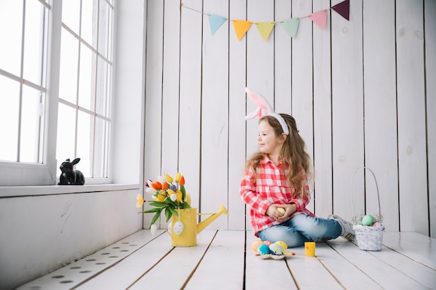 Cute girl in bunny ears sitting on floor with colored eggs