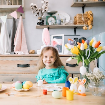 Cute girl in bunny ears sitting at table with colored eggs