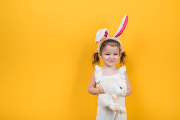 Cute girl in bunny ears standing with rabbit