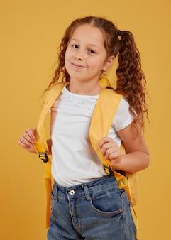 Милая девушка, несущая желтый рюкзак