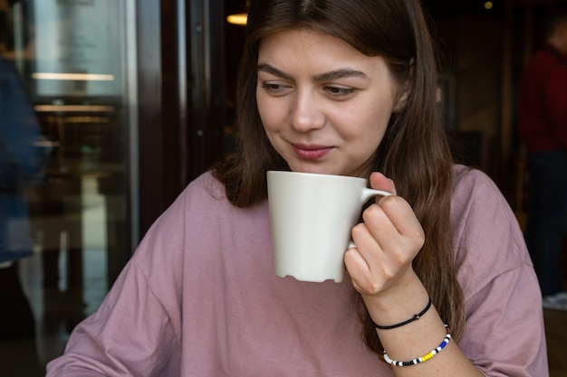 Cute girl in casual style with a cup of hot drink in a cafe
