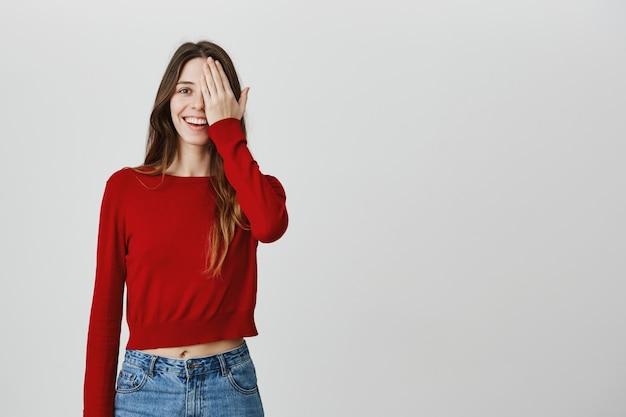 Симпатичная девушка проверяет зрение у оптики, закрывает один глаз и улыбается
