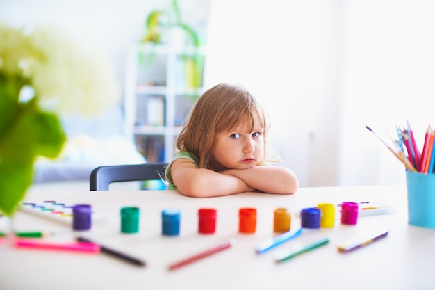 A cute girl child is waiting for permission to start drawing