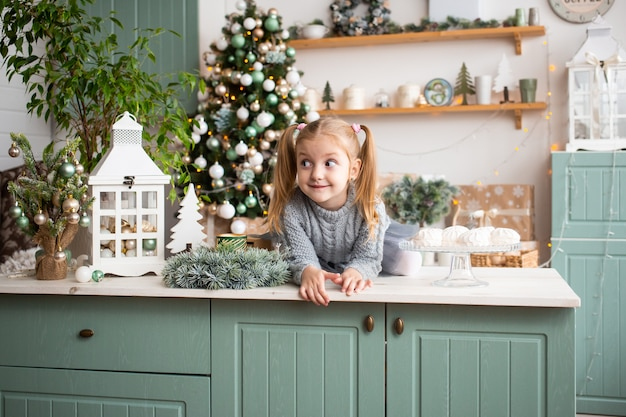 Cute girl in christmas kitchen at home.