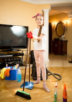 Cute girl cleaning up living room with vacuum cleaner, swab and scoop