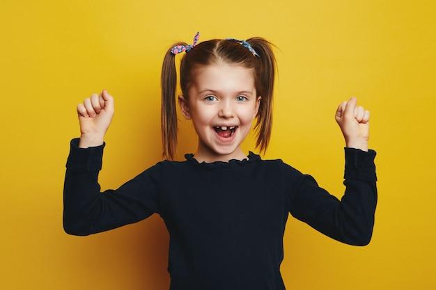 Милая девушка сжимает кулаки и улыбается в камеру, празднуя успех