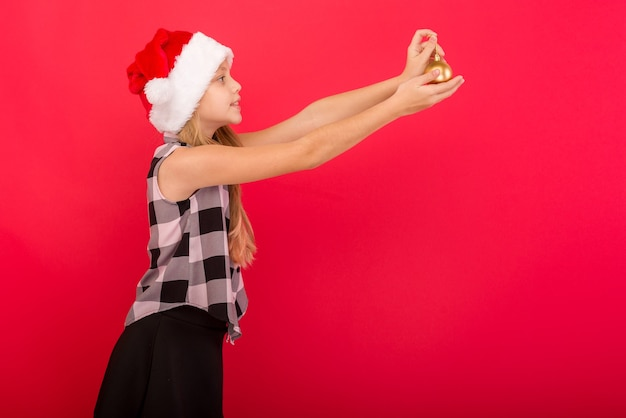 Cute girl on a colored background in a christmas hat holds balls to decorate the xmas tree - image