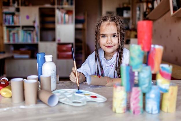 トイレットペーパーのロールを着色するかわいい女の子は、タワーを構築するために紙のブロックのようにそれらを使用します