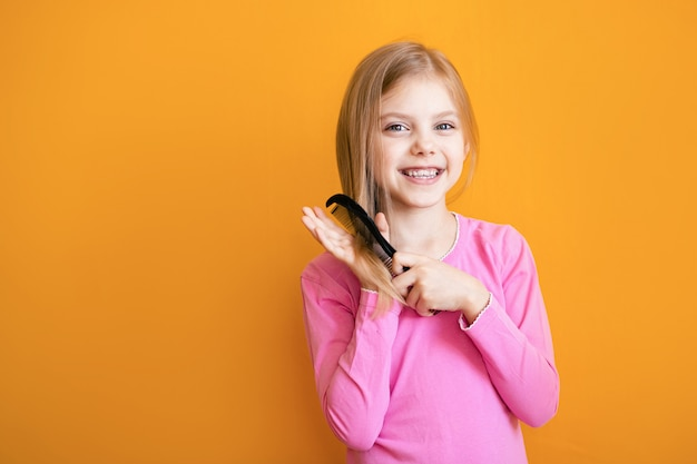 Cute girl combing her soft blond hair on orange wall