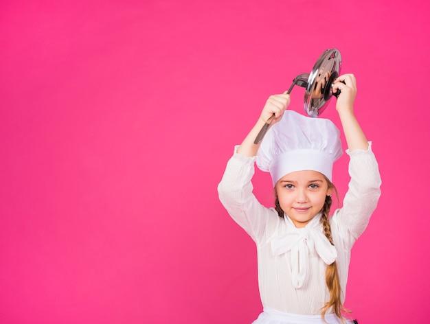 Милая девушка повар с ковшом и крышкой, улыбаясь