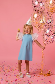Cute girl in costume with balloons and party hat
