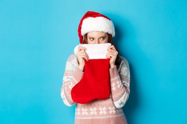 かわいい女の子は、クリスマスの靴下で顔を覆い、狡猾な視線で右を見つめ、サンタの帽子に立って、冬の休日を祝う、青い背景。