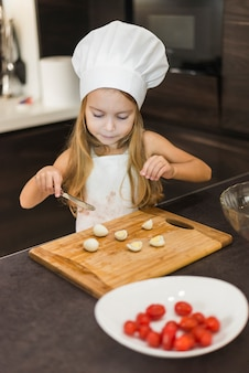Cute girl cutting egg slices on chopping board with knife