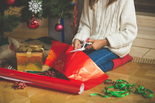リビングルームでクリスマスツリーの下で包装紙を切るかわいい女の子