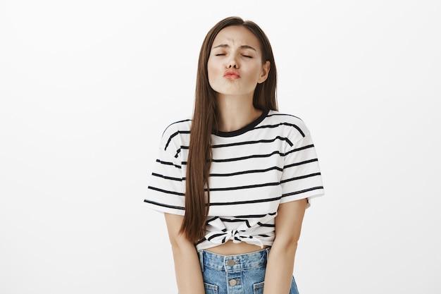 キスについて空想にふけって、目を閉じて唇をふくれっ面するかわいい女の子