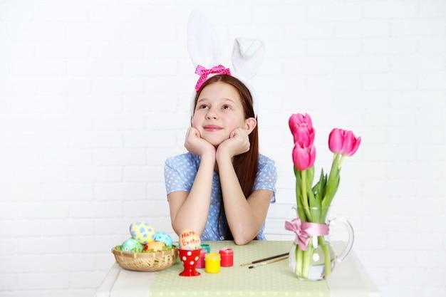 かわいい女の子は、明るい背景で、イースターエッグを飾る