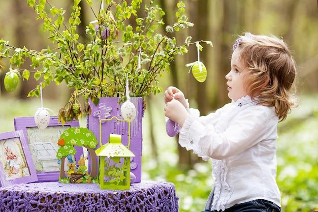 Милая девушка украшает ветви пасхальными яйцами. весна в саду