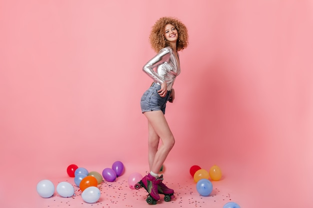 Cute girl in denim shorts and silver top rollerblading on pink space among balloons and confetti.