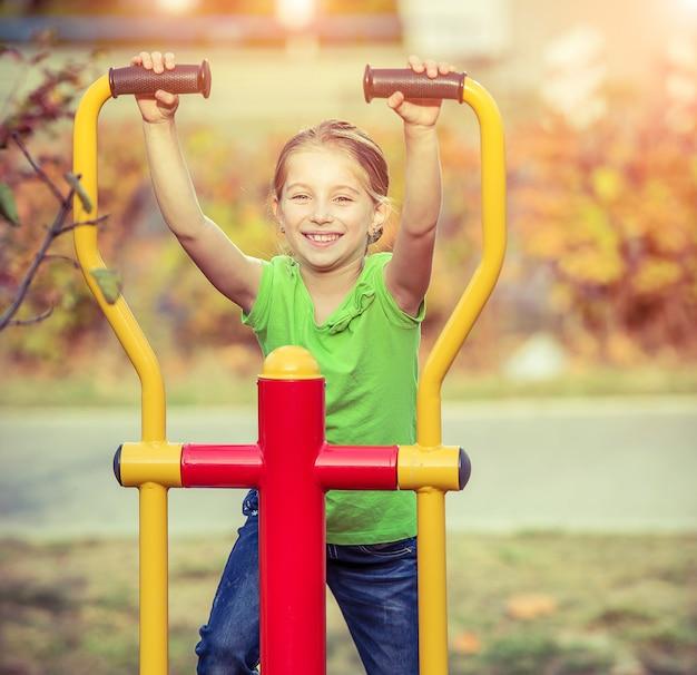かわいい女の子は公園のシミュレーターで運動をします