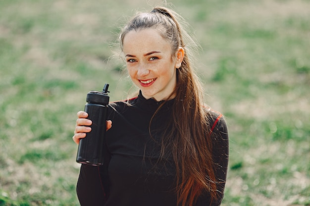 Милая девушка занимается йогой в парке летом