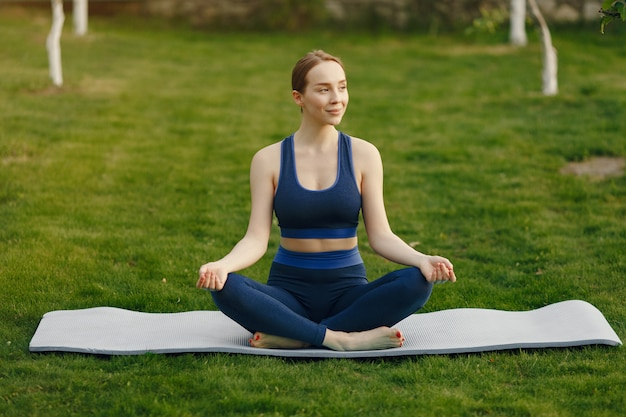 Cute girl doing yoga in a summer park