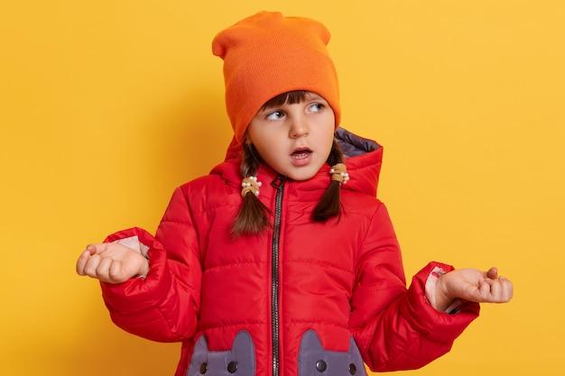 かわいい女の子は、疑問のジェスチャーで彼の肩を疑って肩をすくめる、開いた口で脇を見て、黄色の壁に隔離されたカジュアルなジャケットとキャップを身に着けています
