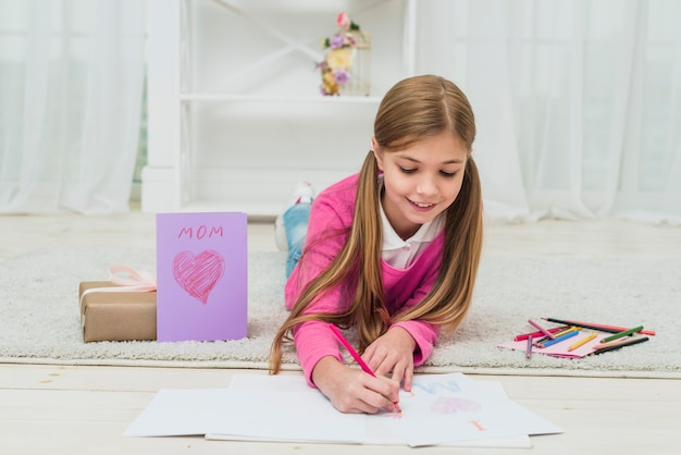 Cute girl drawing on paper near greeting card