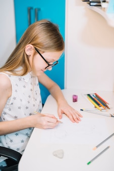Cute girl drawing with pencil at light table