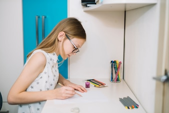 Cute girl drawing with pencil at table
