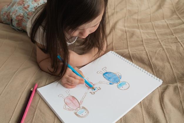 かわいい女の子は鉛筆画を描画します。子供は人を描くことを学びます。子供はベッドに横になり、青鉛筆で描く
