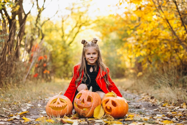 Cute girl dressed in halloween costume outdoors with pumpkins