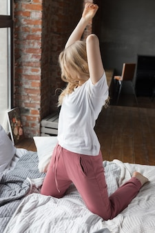 Cute girl dressed in pink pajama pants, white t-shirt sitting on bed with pillow