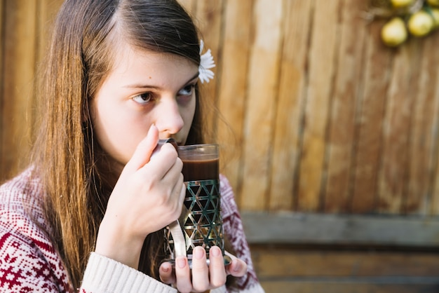 Cute girl drinking glass of chocolate drink