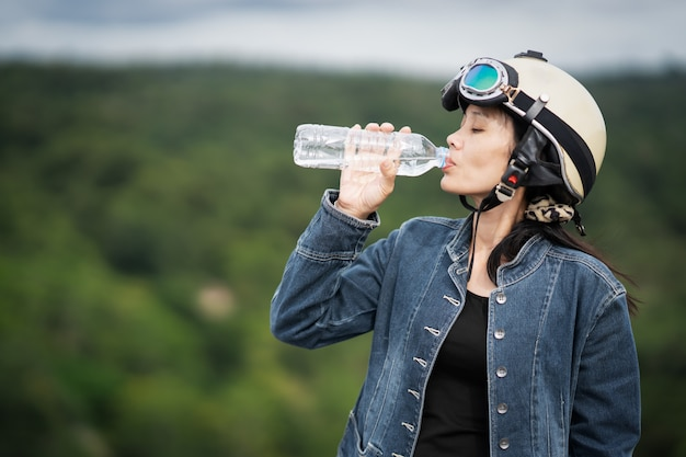 Cute girl drinking water to refresh on blurred beautiful green forest nature background