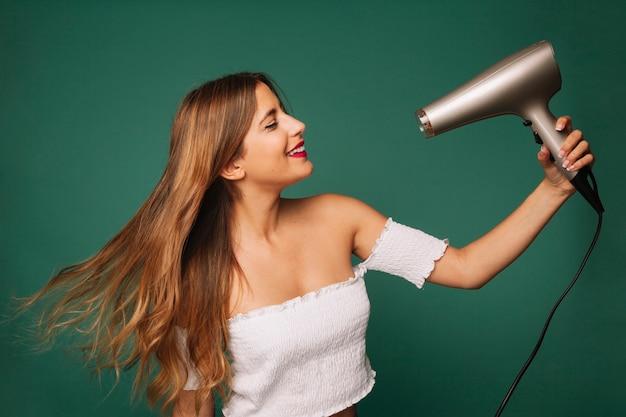 Cute girl drying her hair