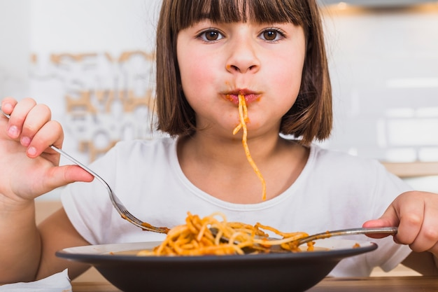 Cute girl eating delicious pasta in kitchen