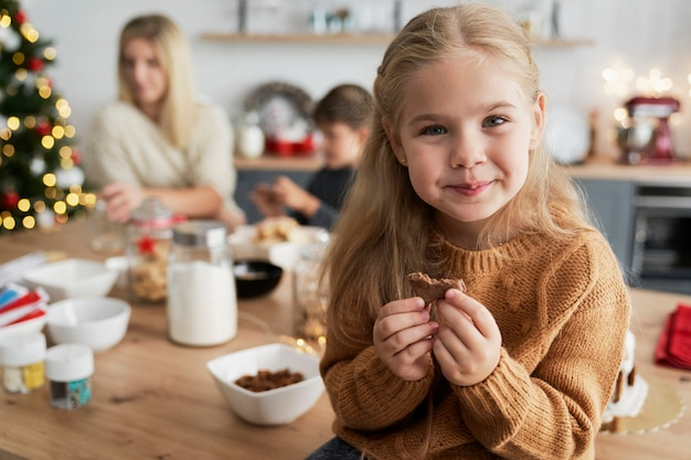 Cute girl eating homemade cookie while sitting on table
