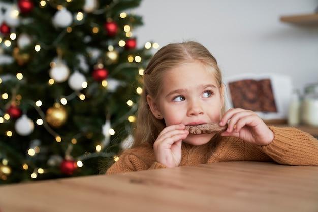 Ragazza carina che mangia biscotto di pan di zenzero fatto in casa