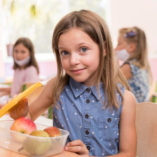 Ragazza carina che mangia al concetto di scuola