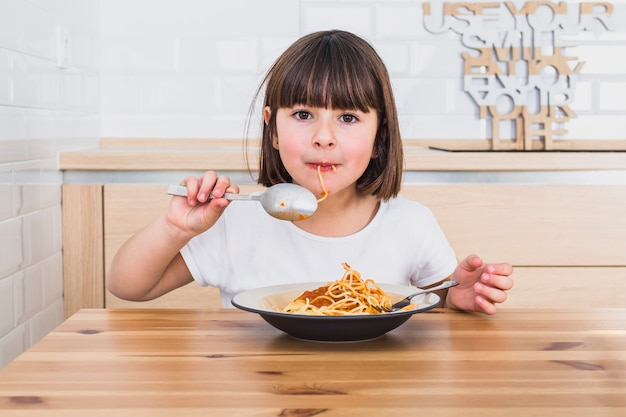 Cute girl eating tasty spaghetti