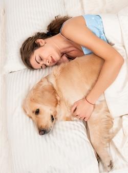 かわいい女の子は寝室の室内で彼女自身の犬のレトリーバーを受け入れる